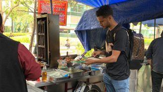 Diego Reyes comiendo tacos en puesto callejero