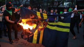 Las manifestantes queman la bandera del América
