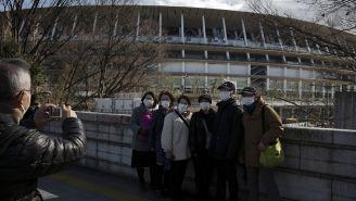 Aficionados japoneses se toman una foto con el Estadio Olímpico de Tokio de fondo