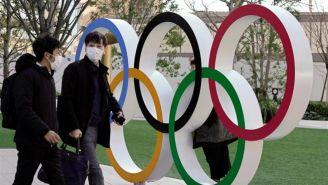 Ciudadanos de Tokio atraviesan por el monumento de los aros olímpicos