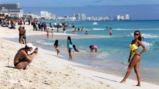 Visitantes en una playa de Cancún