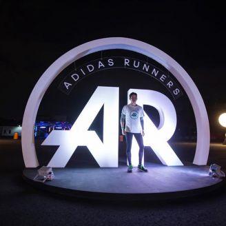 Un corredor posa frente al logo de Adidas