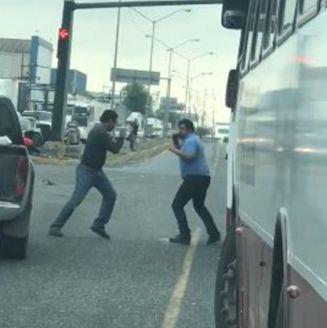 Dos personas pelean a media calle entre el tráfico