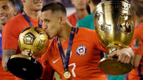 Alexis besa los trofeos obtenidos en la Copa América