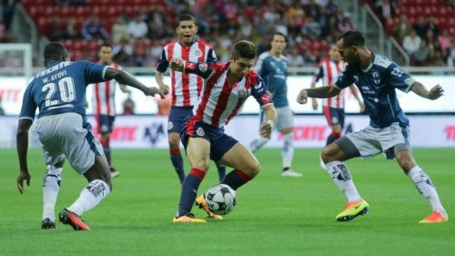 Isaac Brizuela intenta pasar entre dos jugadores rayados