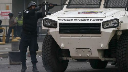 Un policía venezolano se refugia tras un camión, mientras dispara
