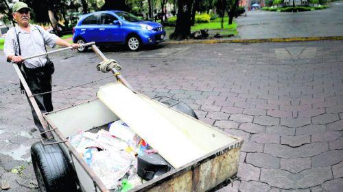 Un hombre arrastra una carreta para recolectar basura