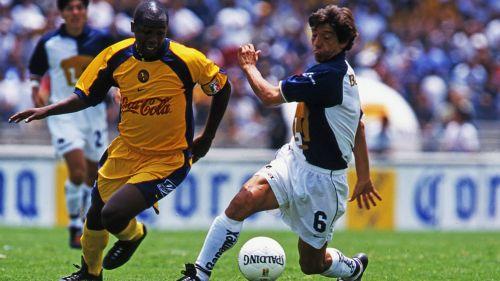 Miguel España disputa el balón contra Fabio Moreno de América