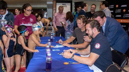 Aaron Peirsol firma autógrafos a niños