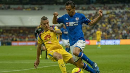 Baca conduce el balón y trata de llevarse la marca de Uribe