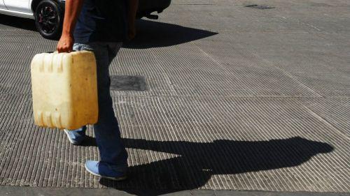 Un hombre trasporta gasolina en un contenedor