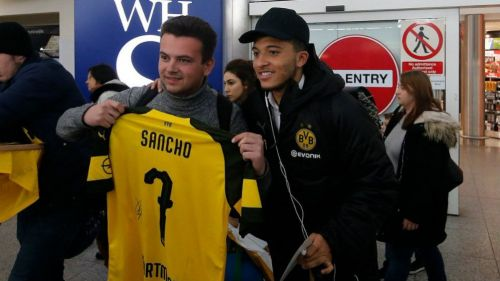 Sancho posa con un fan a su llegada a Londres