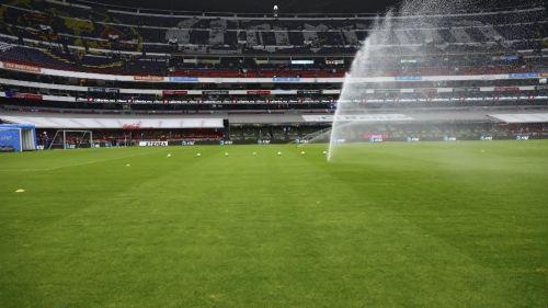 Cancha del Estadio Azteca es regada previo a un encuentro de futbol