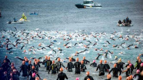 Triatletas nadan durante un Ironman