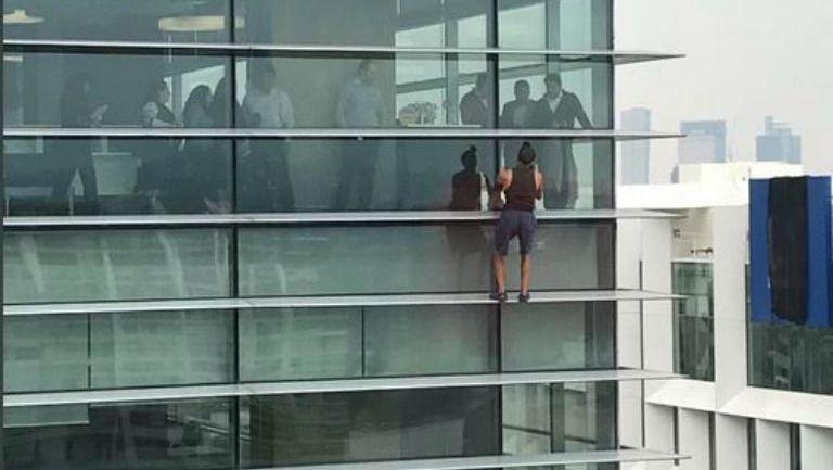 Personas observar a un sujeto escalando un edificio en Polanco
