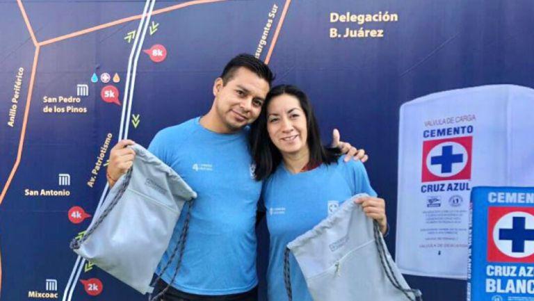 Pareja recibe su paquete para participar en la carrera de Cruz Azul