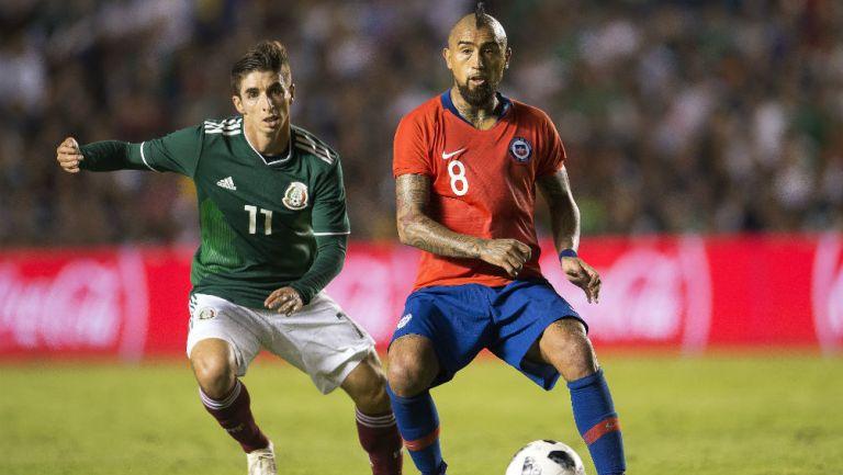 Isaac Brizuela busca quitarle el balón a Arturo Vidal