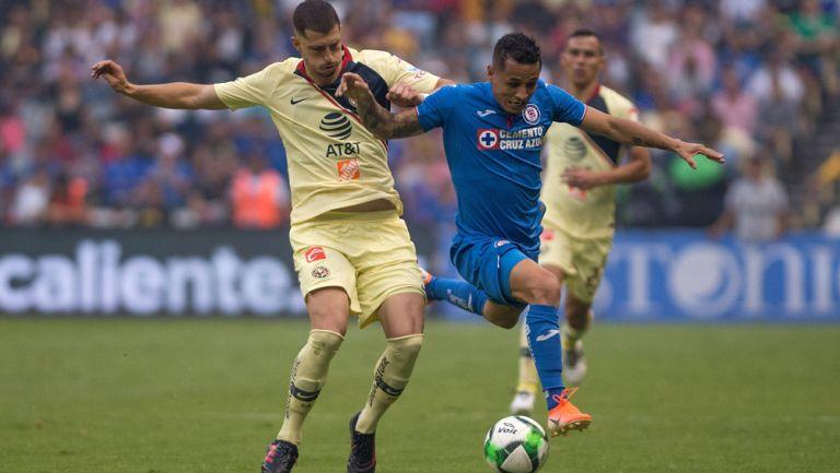 Guido Rodríguez disputa un balón ante Yotún de Cruz Azul