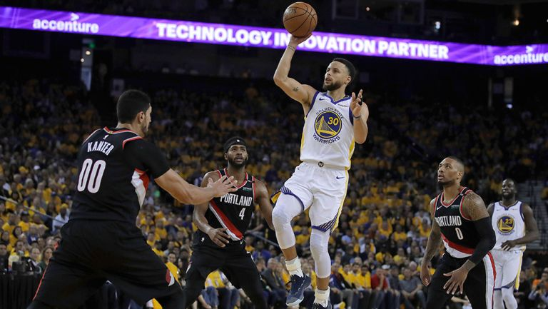 Curry lanza el balón entre defensivos de Portland