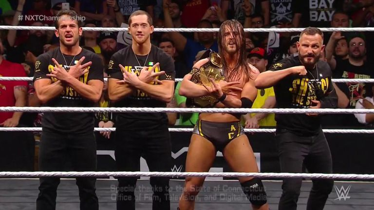 Adam Cole festeja con sus compañeros de The Undisputed Era