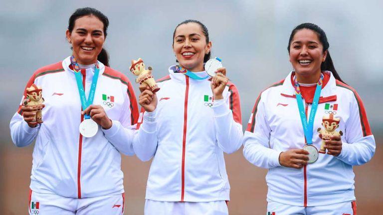 El equipo femenil de tiro con arco muestra sus medallas en el podio