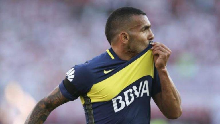 Carlos Tevez celebrando una anotación besando el escudo de Boca
