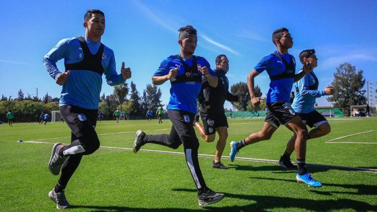 Jugadores de Querétaro corren en un entrenamiento
