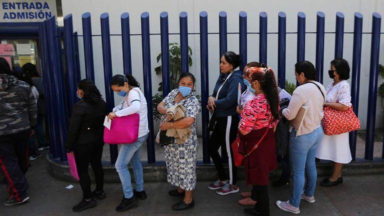 Personas afuera de un hospital con cubrebocas
