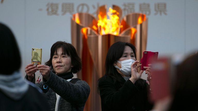 Japoneses se toman selfies con la llama olímpica