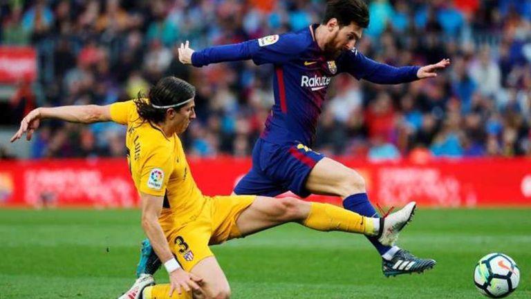 Filipe Luis y Messi pelea un balón en España