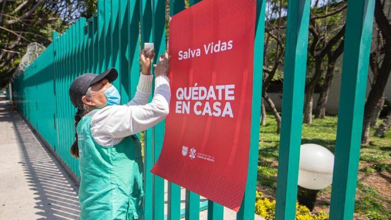 Persona coloca un cartel de 'Quédate en casa' en CDMX