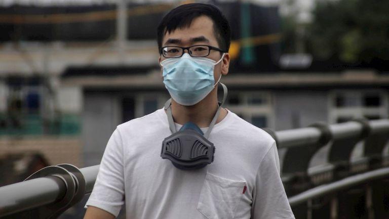 Persona con cubrebocas camina en las calles de Beijing