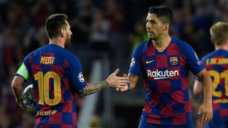 Luis Suárez saluda a Lionel Messi en juego con el Barcelona