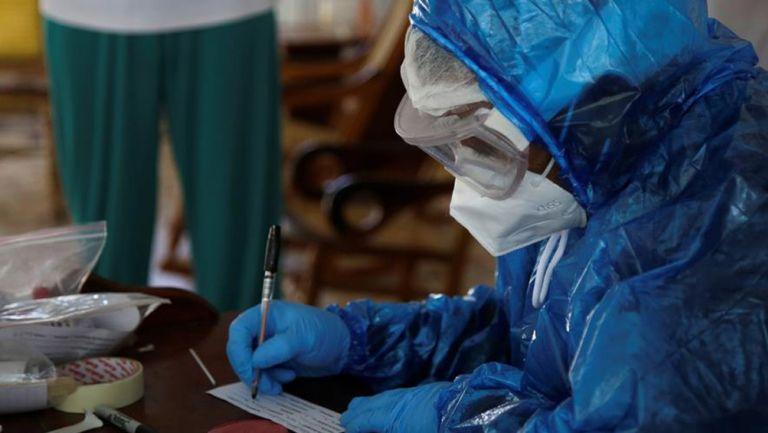Profesional de la salud mientras llena un formulario de prueba para Covid-19