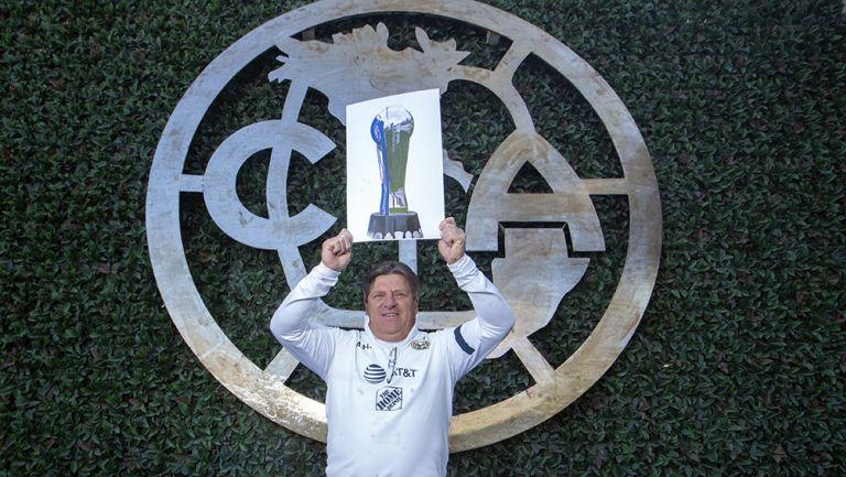 Piojo Herrera sostiene una imagen con el trofeo de Liga MX