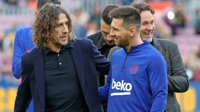 Carles Puyol platica con Lionel Messi en Barcelona