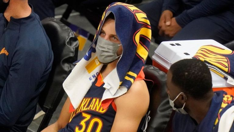Steph Curry usa cubrebocas en la banca de Warriors