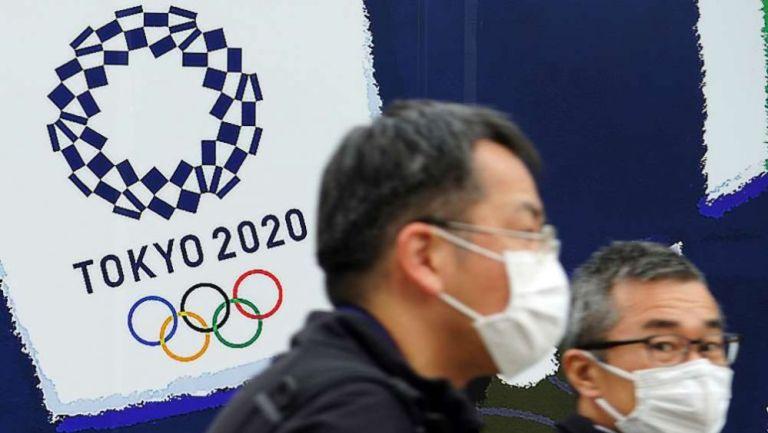 Ciudadanos de Tokio caminan frente a un cartel de los Juegos Olímpicos