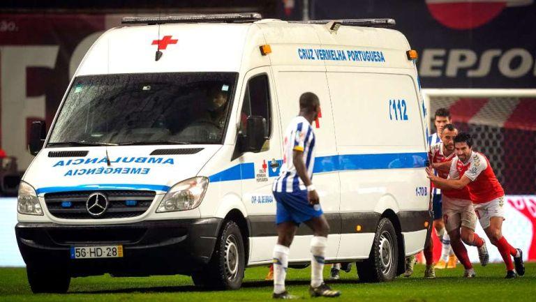 Jugadores empujando la ambulancia fuera del terreno de juego