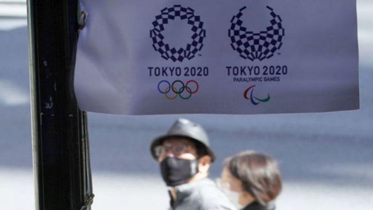 Habitantes de Japón pasan por un cartel de Tokio 2020