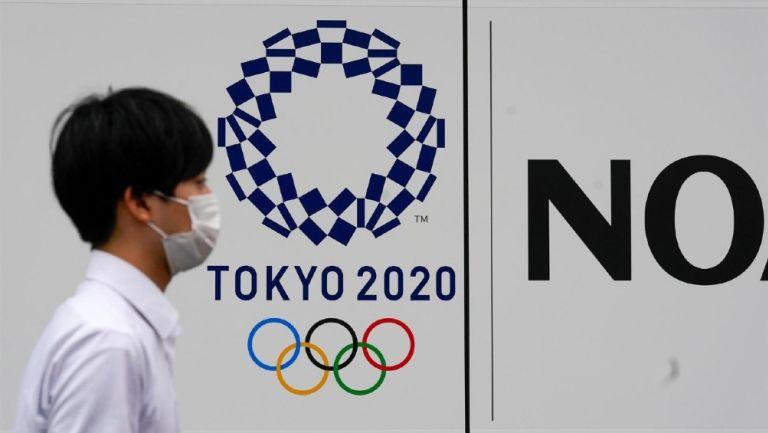 Peatón junto a logo de los Juegos Olímpicos Tokio 2020