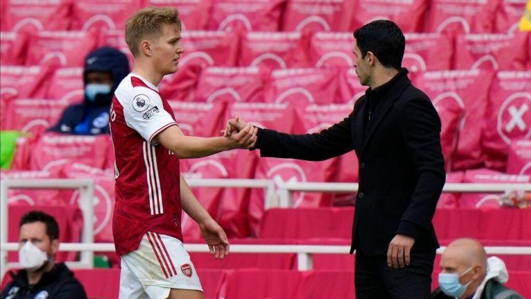 Martin Odegaard estrecha la mano de Mikel Arteta