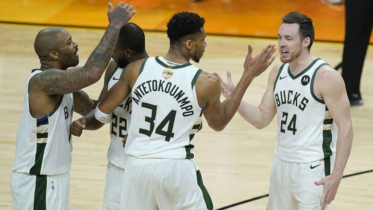 Jugadores de Bucks de Milwaukee festejan una canasta