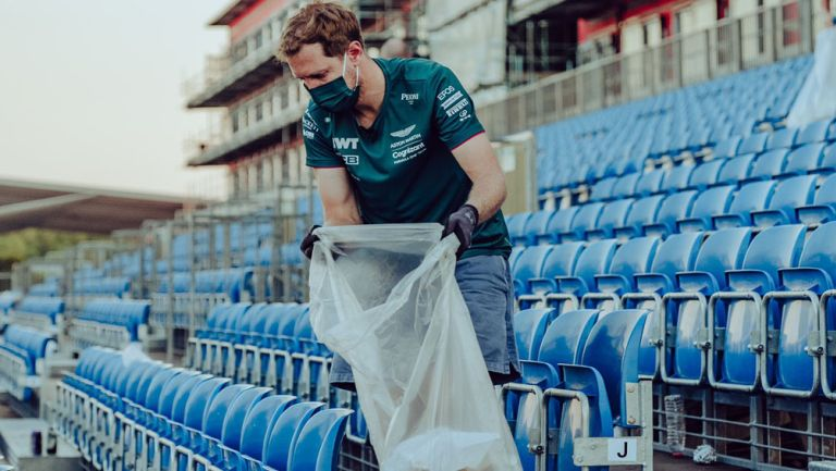 Sebastian Vettel recoge la basura en las gradas