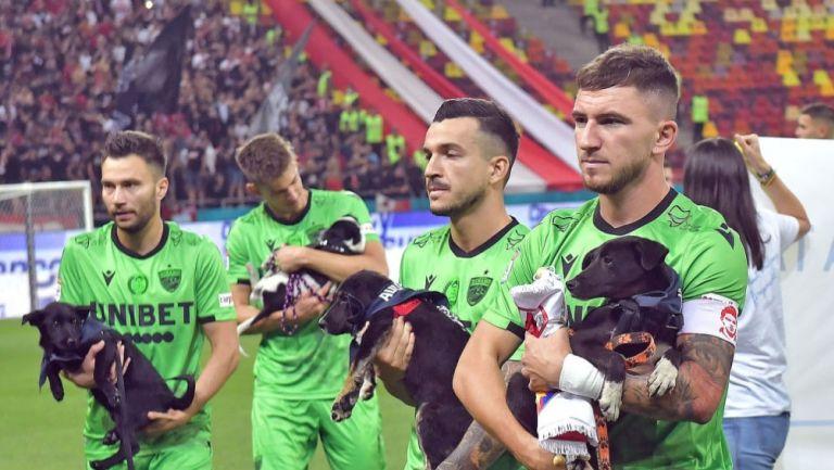 Jugadores del Dínamo Bucarest en la cancha con los cachorros