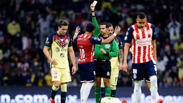 César Ramos mostrando una tarjeta en el Clásico Nacional